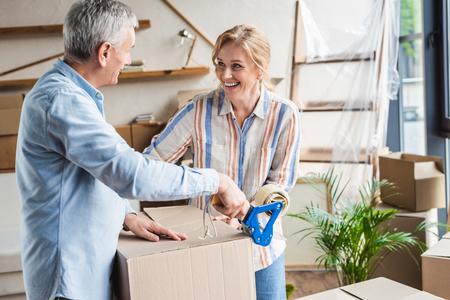Photo pour happy elderly couple packing cardboard boxes during relocation - image libre de droit