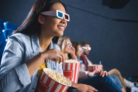 Foto de smiling asian woman in 3d glasses with popcorn watching movie in cinema - Imagen libre de derechos