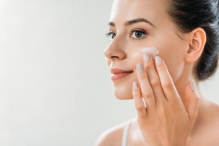 Foto de beautiful smiling young woman applying face cream and looking away - Imagen libre de derechos