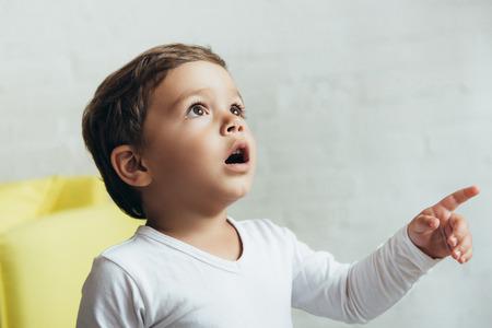 Photo pour portrait of little shocked boy pointing and looking up - image libre de droit
