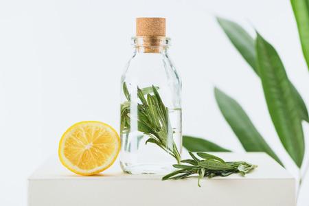 Foto de transparent bottle of natural herbal essential oil with green twig and lemon on white cube - Imagen libre de derechos
