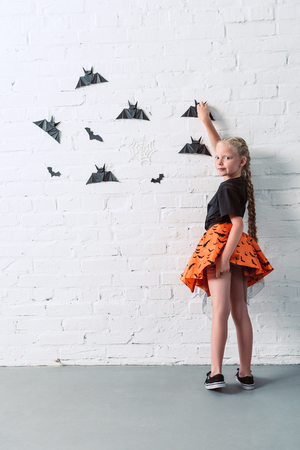 Photo pour back view of child in skirt hanging black paper bats on white brick wall, halloween holiday concept - image libre de droit