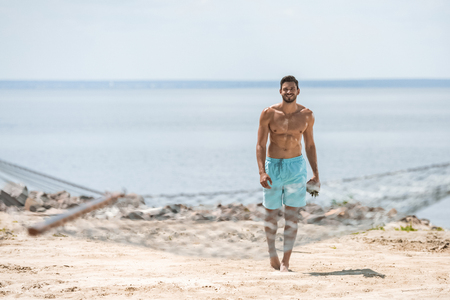 handsome shirtless man walking on beach, with hammock on foreground