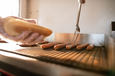 Foto de cropped image of chef preparing hod dog in food truck and taking sausage - Imagen libre de derechos