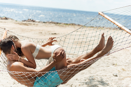 Photo pour couple of lovers kissing and resting in hammock on beach near the sea - image libre de droit