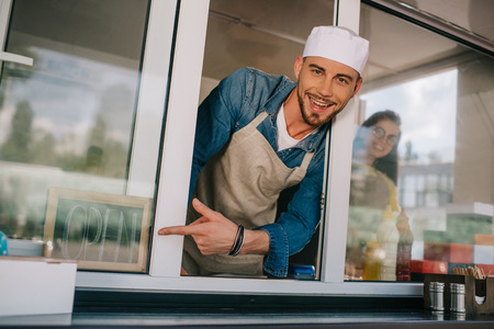 Photo pour cheerful young man smiling at camera and pointing with finger at sign open in food truck - image libre de droit