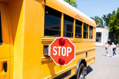 partial view of school bus with stop sign standing on parking with blurred students running on background