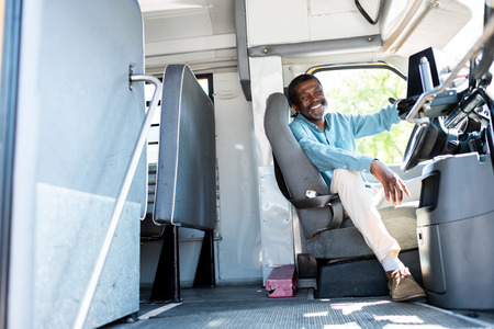 Photo pour happy mature african american bus driver looking at camera while sitting inside bus - image libre de droit