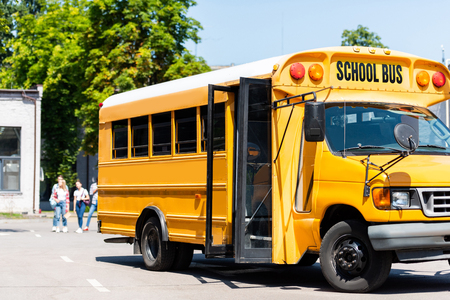 Photo pour school bus standing on parking with blurred students walking on background - image libre de droit