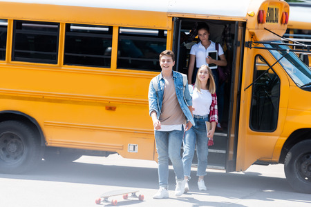 Photo pour group of teen students walking out of school bus after school - image libre de droit