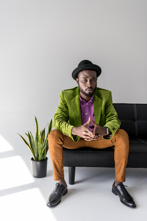Foto de stylish african american in hat sitting on black sofa o grey background - Imagen libre de derechos