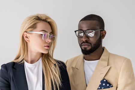 Photo pour portrait of beautiful stylish young multiethnic couple in eyeglasses isolated on grey - image libre de droit