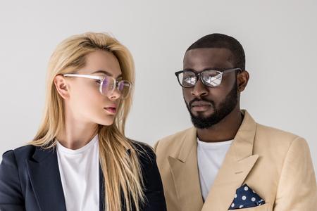 Foto de portrait of beautiful stylish young multiethnic couple in eyeglasses isolated on grey - Imagen libre de derechos