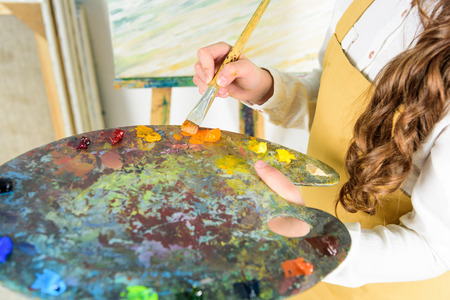 Photo pour cropped image of child taking oil paints from palette in workshop of art school - image libre de droit