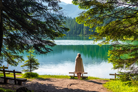 Photo pour back view of woman in blanket looking at beautiful glacial Black Lake in Montenegro - image libre de droit