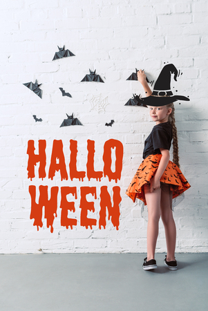Photo pour back view of child in skirt hanging black paper bats on white brick wall, with halloween lettering - image libre de droit