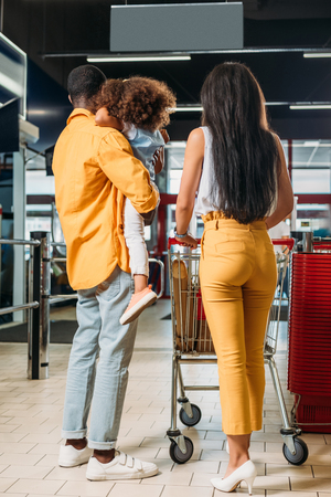 Photo for rear view of african american family with shopping trolley in supermarket - Royalty Free Image