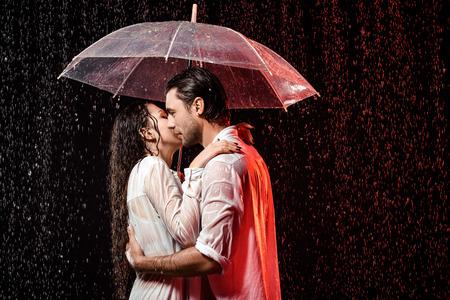 Foto de side view of romantic couple in white shirts with umbrella standing under rain on black backdrop - Imagen libre de derechos