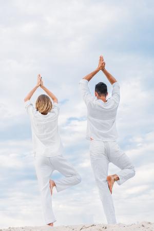 Foto de rear view of couple practicing yoga in tree pose (Vrksasana) on sandy dune - Imagen libre de derechos