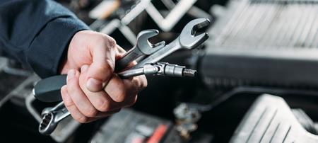 Foto de partial view of worker holding tools and wrenches in hand - Imagen libre de derechos