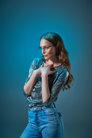 Photo pour beautiful woman in stylish outfit and eyeglasses looking away isolated on blue - image libre de droit