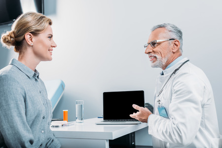 happy mature male doctor pointing at laptop with blank screen to female patient sitting near in office