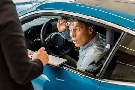 Photo pour cropped shot of female car dealer showing car dealership contract to shocked man in showroom - image libre de droit