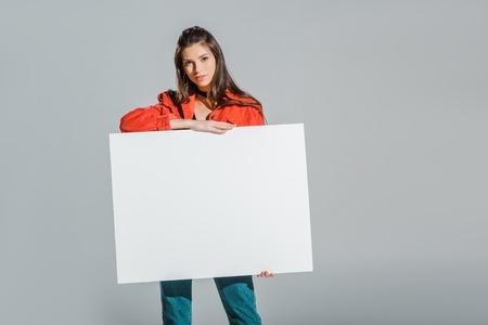 Foto de beautiful girl holding blank placard isolated on grey - Imagen libre de derechos