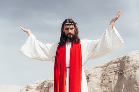 low angle view of Jesus in robe, red sash and crown of thorns standing with raised hands in desert