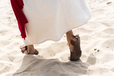 Photo pour cropped image of Jesus in robe, sandals and red sash walking on sand in desert - image libre de droit