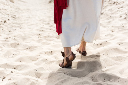 Photo for cropped image of Jesus in robe, sandals and red sash walking on sand in desert - Royalty Free Image