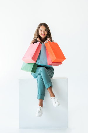 Foto de smiling shopaholic sitting on white cube with shopping bags, isolated on white - Imagen libre de derechos