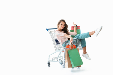 Photo pour happy beautiful girl sitting in shopping cart with bags, isolated on white - image libre de droit