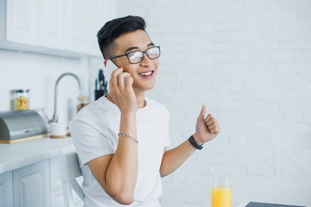 happy young asian man talking by smartphone while sitting in kitchen