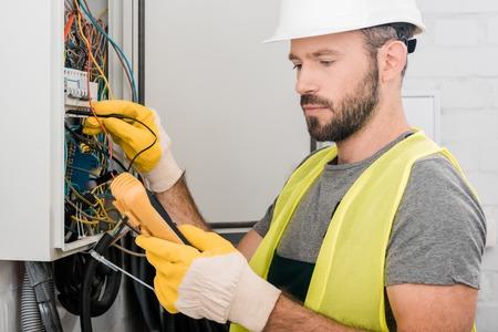 Photo pour handsome electrician checking electrical panel with multimetr in corridor - image libre de droit