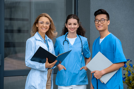 Photo pour smiling teacher with two multicultural students looking at camera at medical university - image libre de droit