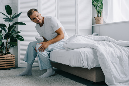 Photo pour young man in pajamas sitting on bed and looking away while suffering from knee pain at home - image libre de droit
