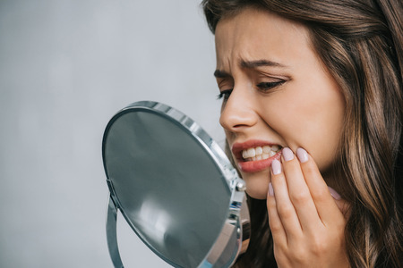 Photo pour close-up view of young woman having toothache and looking at mirror - image libre de droit
