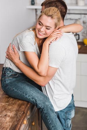 Photo pour happy girlfriend sitting on kitchen counter and hugging boyfriend - image libre de droit