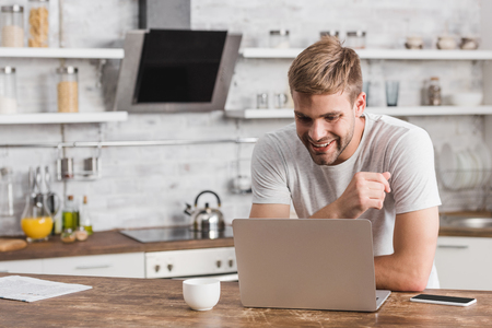 Photo for smiling handsome freelancer looking at laptop in kitchen - Royalty Free Image