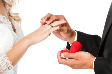 Photo pour cropped shot of groom putting on wedding ring on brides finger isolated on white - image libre de droit