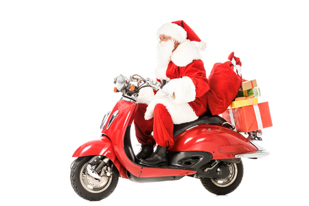 Photo pour side view of santa claus riding vintage red scooter with sacks and gift boxes isolated on white - image libre de droit