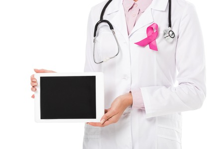 Foto per cropped shot of doctor with pink ribbon holding digital tablet with blank screen isolated on white, breast cancer awareness concept - Immagine Royalty Free