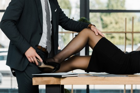 partial view of passionate businessman and businesswoman at workplace in office