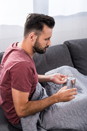 sick young man sitting on couch with glass of water and pills