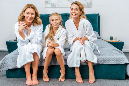 Foto de happy child with mother and grandmother in bathrobes sitting on bed at home and looking at camera - Imagen libre de derechos