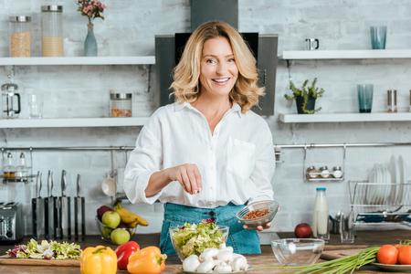 Foto de beautiful adult woman spilling spice onto lettuce in bowl at kitchen and looking at camera - Imagen libre de derechos