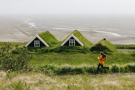 Foto de distant view of young woman running near Black farmhouses in Skaftafell National Park in Iceland - Imagen libre de derechos