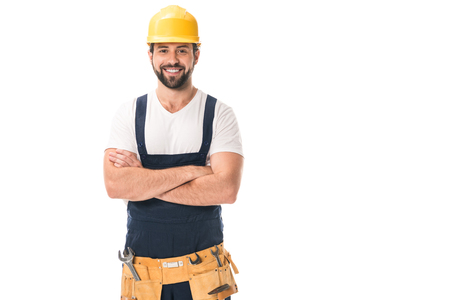 Photo pour handsome happy workman in hard hat and tool belt standing with crossed arms and smiling at camera isolated on white - image libre de droit