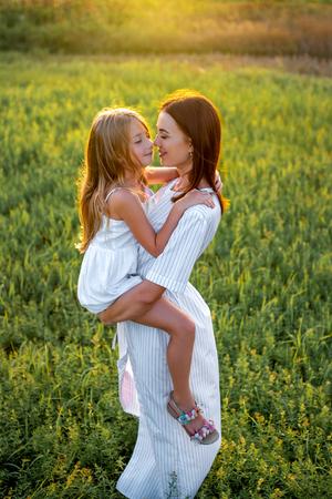 Foto de high angle view mother and daughter embracing in green meadow - Imagen libre de derechos